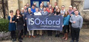 Staff outside the chapel at IS Oxford, celebrating becoming an Employee Owned Trust